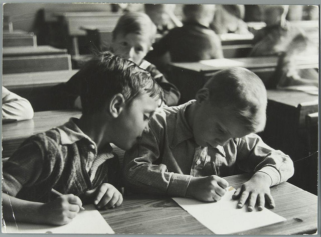 Children writing on paper with a pen in classroom - netherlands - 1937